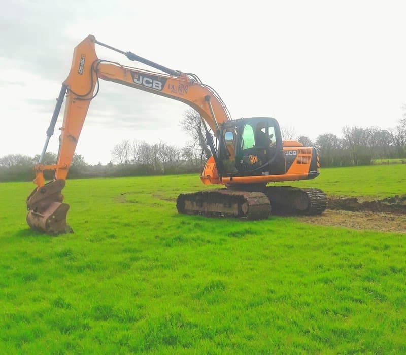 Dunn 2000 JCB Excavator digging in field
